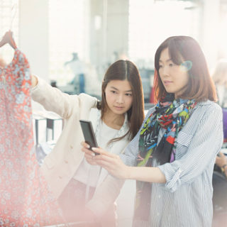 Fashion designers photographing dress with camera phone
